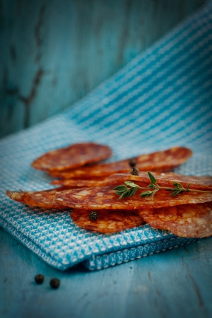 Chorizo salami sausage on blue rustic background. Meat cold cuts.  photo