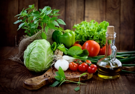 Verse ingrediënten voor het koken in de rustieke omgeving: tomaten, basilicum, olijfolie, knoflook en ui, kool, letttuce