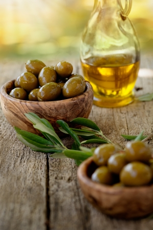 Fresh olives and olive oil  on rustic wooden background  Olives in olive wood  Stock Photo