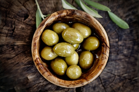 olive leaves: Fresh olives on rustic wooden background  Olives in olive wood  Stock Photo