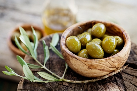 greek cuisine: Fresh olives and olive oil  on rustic wooden background. Olives in olive wood.
