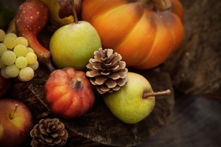 harvest basket: Autumn nature. Fall fruit on wood. Pumpkins, apples,grapes, courgettes and pears
