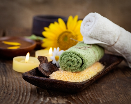 Spa and wellness setting with natural bath salt, candles and towel, massager and sunflower. photo