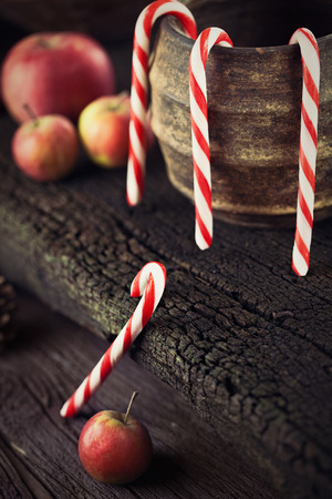 Christmas rustic decoration. Christmas candies and apples on wood background photo