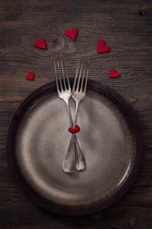 Valentijnsdag diner met tafel setting in rustieke houten stijl met bestek