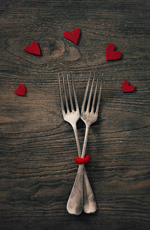 Valentines day dinner with table setting in rustic wood style with cutlery