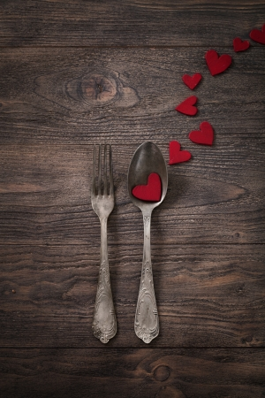 dating and romance: Valentines day dinner with table setting in rustic wood style with cutlery