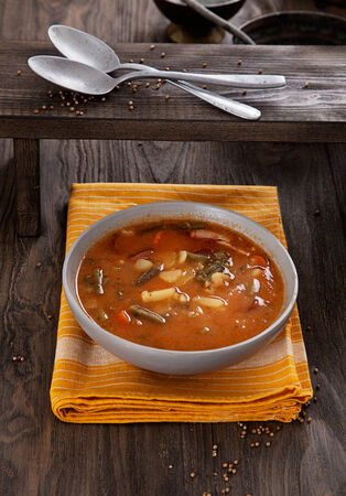 stew pan: Delicious vegetable stew soup with sausage and french beans on wood. Stock Photo
