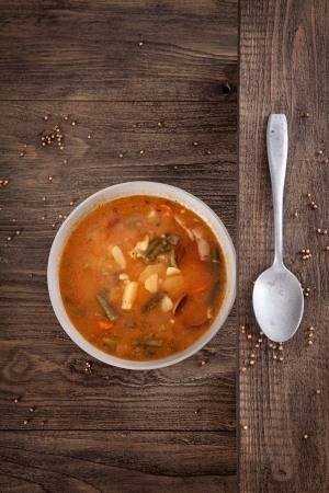 sausage pot: Delicious vegetable stew soup with sausage and french beans on wood. Stock Photo