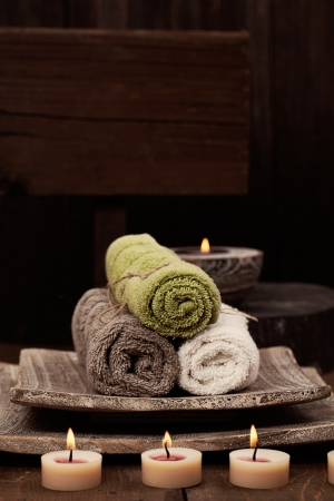Spa and wellness setting with natural soap, candles and towel. Wooden dayspa nature setting photo