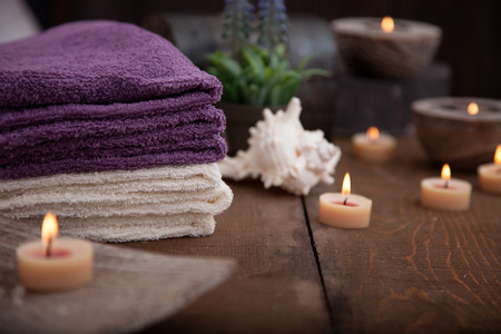 bath and body: Spa and wellness setting with natural bath salt, candles, towels and flower. Wooden dayspa nature set Stock Photo