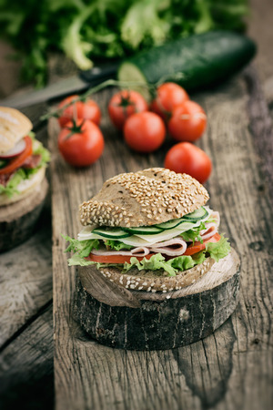 Delicious ham, cheese and salami sandwich with vegetables, lettuce, cherry tomatoes in natural setting with wooden  photo