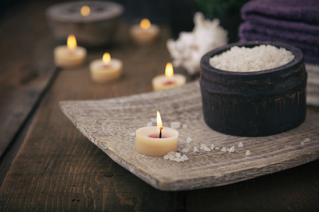 spa stones: Spa and wellness setting with natural bath salt, candles, towels and flower. Wooden dayspa nature set Stock Photo