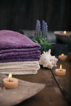 candles spa: Spa and wellness setting with natural bath salt, candles, towels and flower. Wooden dayspa nature set Stock Photo
