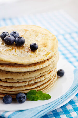 Breakfast food. Pancakes with honey and blueberries. photo
