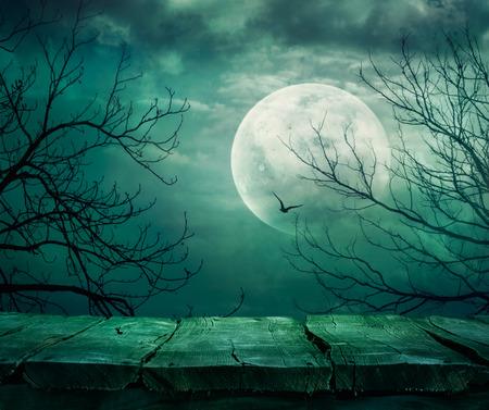 Halloween achtergrond. Spooky bos met volle maan en de houten tafel