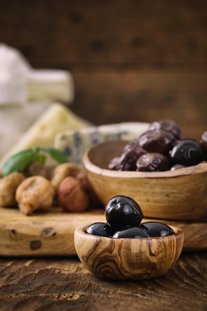 Black olives , herbs and cheese on wood photo