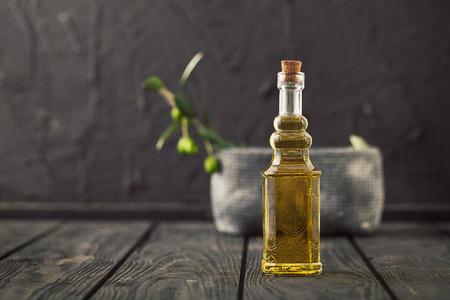 Extra vierge olijfolie gezond met verse olijven op donkere houten achtergrond