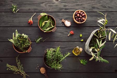 herbs: Aceite de oliva con hierbas. Ingredientes mediterráneos: el romero, las aceitunas, el tomillo, la salvia, la sal, el orégano Foto de archivo