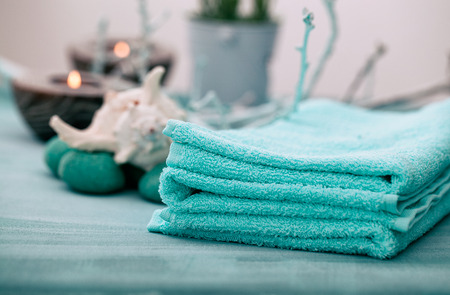 dayspa: Spa and wellness setting with flowers, candles and towel. Blue dayspa nature set with copyspace Stock Photo