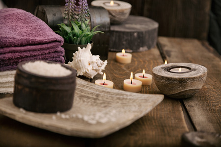 Spa and wellness setting with natural bath salt, candles, towels and flower. Wooden dayspa nature set Фото со стока
