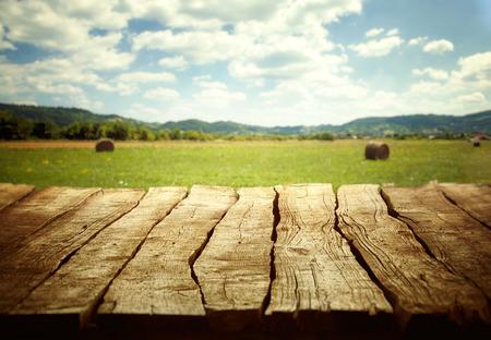 Wooden empty table. Wooden display with spring fields bokeh. Standard-Bild