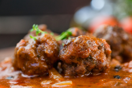 Italian cooking with beef meat balls with cherry tomatoes, tomato sauce and basil Imagens