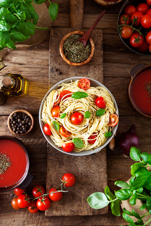 Italienische Küche. Nudeln mit Olivenöl, Knoblauch, Basilikum und Tomaten und Tomatensuppe.