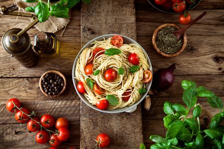jitomates: Cocina italiana. Pasta con aceite de oliva, ajo, albahaca y tomates y la sopa de tomate. Foto de archivo