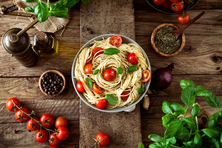 Italiaanse keuken. Pasta met olijfolie, knoflook, basilicum en tomaten en tomatensoep.