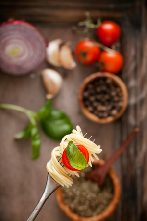 pasta fork: Italian cuisine. Pasta on fork. Pasta with olive oil, garlic, basil and tomatoes. Spaghetti with tomatoes Stock Photo