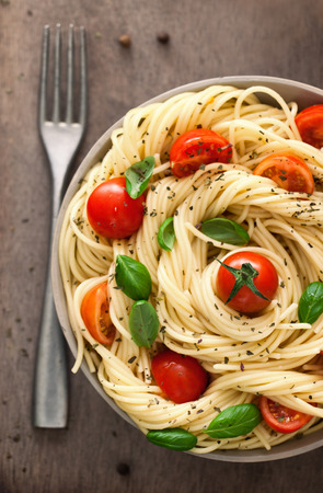 Italian cuisine. Pasta with olive oil, garlic, basil and tomatoes