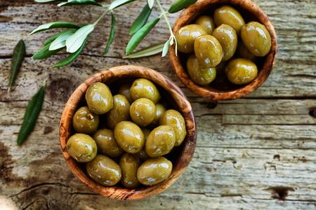 comida italiana: Aceitunas frescas en el fondo de madera rústica Foto de archivo