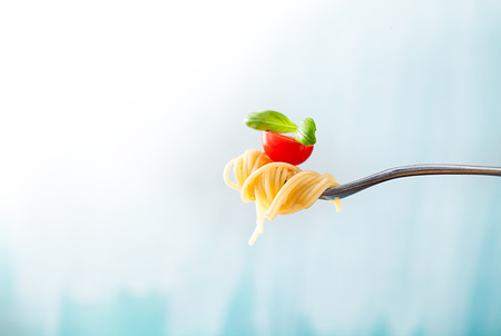 Pasta on fork with olive oil, garlic, basil and tomatoes 免版税图像