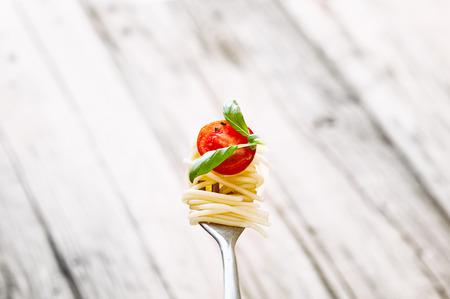 イタリア料理。フォークでパスタ。オリーブ オイル、ニンニク、バジルとトマトのパスタ。トマト スパゲッティ 写真素材