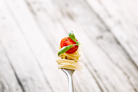 fresh pasta: Italian cuisine. Pasta on fork. Pasta with olive oil, garlic, basil and tomatoes. Spaghetti with tomatoes Stock Photo