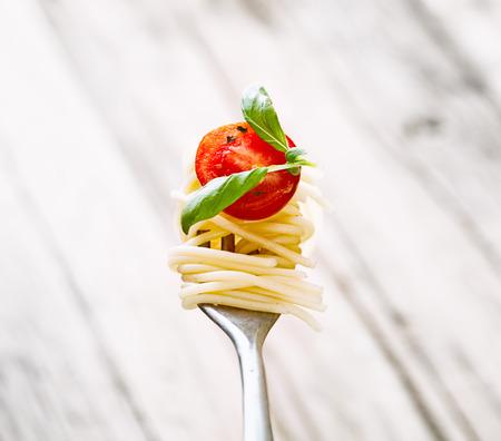pastas: Cocina italiana. Pastas en el tenedor. Pasta con aceite de oliva, ajo, albahaca y tomates. Espagueti con los tomates