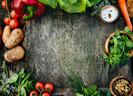 Gezonde voedingsingrediënten achtergrond. Groenten, kruiden en specerijen. Biologische groenten op hout