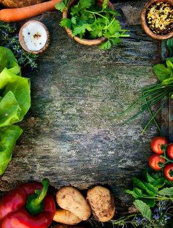 Healthy food ingredients background. Vegetables, herbs and spices. Organic vegetables on wood Standard-Bild