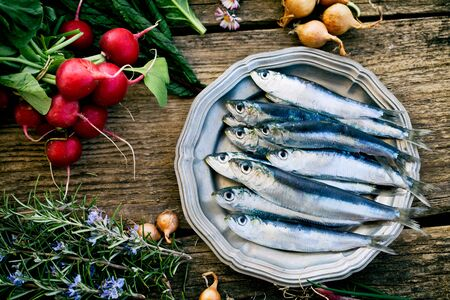 fresh: Fresh sardines. Fish with vegetables. Mediterranean fish on plate
