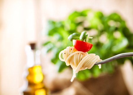 Italian cuisine. Pasta on fork. Pasta with olive oil, garlic, basil and tomatoes. Spaghetti with tomatoes 스톡 콘텐츠