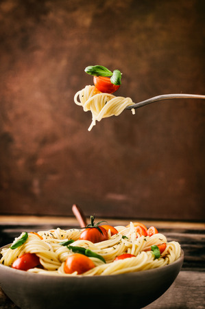 Italian cuisine. Pasta on fork. Pasta with olive oil, garlic, basil and tomatoes. Spaghetti with tomatoes Imagens