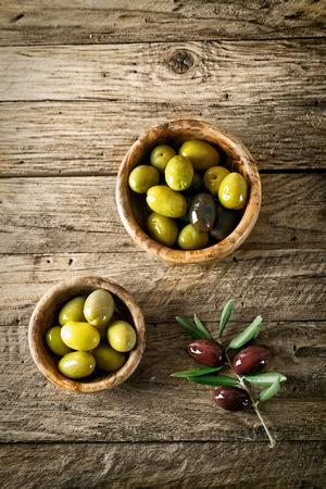 hoja de olivo: aceitunas en madera vieja. Mesa de madera con las aceitunas y el aceite de oliva
