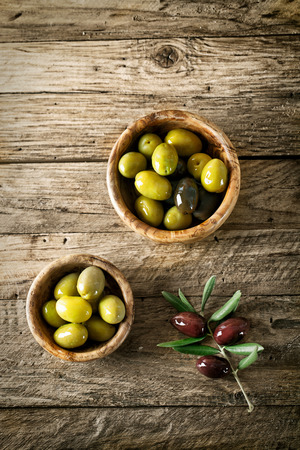 olive oil bottle: olives on old wood. Wooden table with olives and olive oil