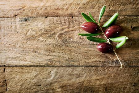 Oliven auf Ölzweig. Holztisch mit Oliven