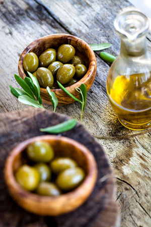 extra virgin olive oil: Fresh olives and olive oil  on rustic wooden background. Olives in olive wood.