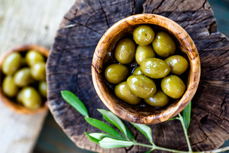 Fresh olives on rustic wooden background. Olives in olive wood. Stockfoto
