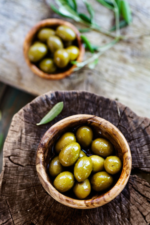 olive green: Fresh olives on rustic wooden background. Olives in olive wood. Stock Photo