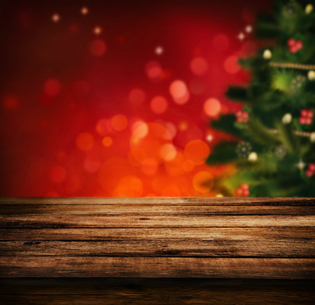 light red: Christmas holiday background with empty wooden deck table over Christmas tree. Empty display for montage. Rustic vintage Xmas background.