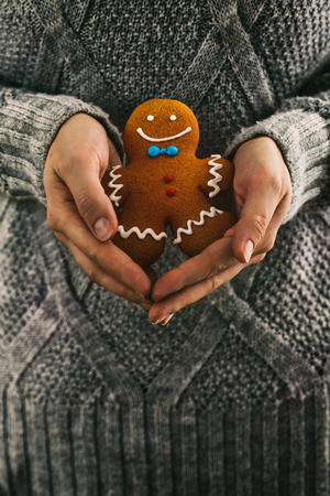 christmas baker's: Christmas baking. Gingerbread man in bakers hands. Xmas cookies. Festive baked cookies.